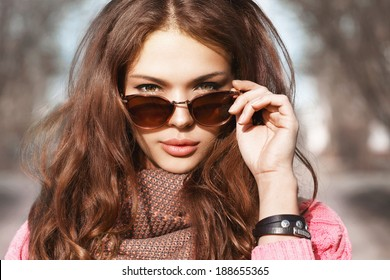 Closeup portrait of beautiful brunette girl standing on the street. Holding sunglasses with her hand and posing. Looking at camera. Urban city scene. Warm sunny weather. Outdoors