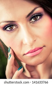 close-up portrait of a beautiful brunette model touching her cheeck with deep dark brown eyes gazing back