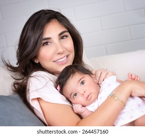 Closeup portrait of beautiful brunette mother with cute newborn daughter relaxing on sofa at home, happy young arabic family