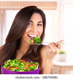 Closeup portrait of beautiful brunette woman eating salad at home on the kitchen, organic food, healthy lifestyle, dieting concept