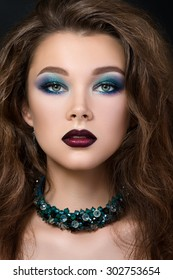 Close-up portrait of beautiful brunette woman with modern fashion make up. Smokey eyes and dark red lips.