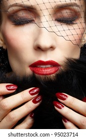 close-up portrait of beautiful brunette woman in veil touching black fur coat with manicured fingers and closing her eyes