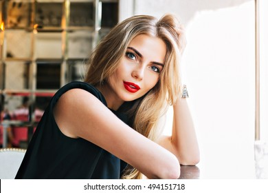 Closeup portrait beautiful businesswoman leaning on table in cafeteria. She has red lips, long blonde hair, looking to camera