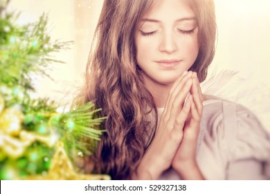 Closeup portrait of a beautiful calm girl with closed eyes praying near Christmas tree, gentle young angel wishing peace and harmony for everyone, happy religious holiday