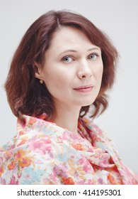 Closeup portrait of beautiful calm middle aged white caucasian brunette woman with green eyes covered with silk cotton scarf on her neck shoulders looking in camera on light white background
