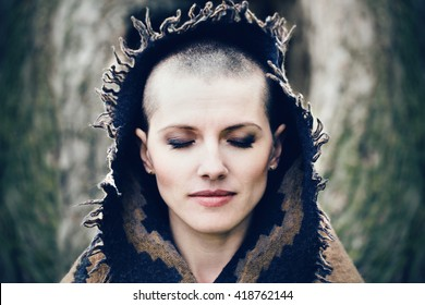 Closeup portrait of beautiful Caucasian white young bald girl woman with shaved hair head with closed eyes, head covered with scarf shawl, spiritual mood state of mind, conceptual, peaceful warrior