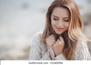 Close-up portrait of beautiful caucasian woman walking outdoors. Beautiful woman in a sweater. Fashion portrait stylish pretty woman outdoor. Young woman having fun in city. Street fashion.