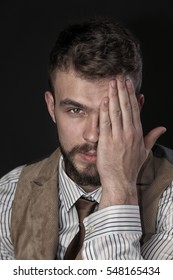 closeup portrait of the beautiful charismatic young man with a beard, covering half of his face with his hand
