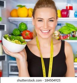 Closeup portrait of beautiful cheerful girl holding in hand bowl with fresh tasty green salad, dietitian recommending eating vegetables, healthy organic nutrition concept