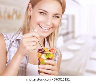 Closeup portrait of beautiful cheerful woman enjoying tasty juice fruits salad, having breakfast at home, healthy eating concept