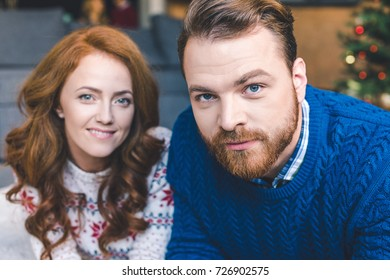 close-up portrait of beautiful couple in warm sweaters looking at camera
