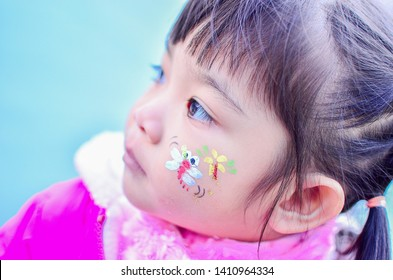Closeup Portrait Beautiful Cute Little Girl Kid with Dragonfly Tattoo Paint on face in winter suit