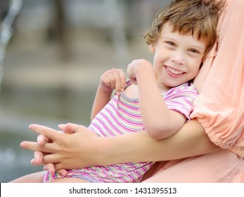 Close-up portrait of beautiful disabled girl in the arms of his mother having fun in fountain of public park at sunny summer day. Child cerebral palsy. Inclusion.