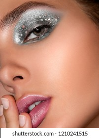 Close-up portrait of a beautiful fashion model with glossy makeup. Model looking at camera wearing trendy glamorous festive festival makeup eyeshadow lipstick lipgloss highlighter foundation mascara