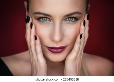 Closeup portrait of beautiful fashion model over dark red background, pretty woman with stylish makeup, beauty salon photo