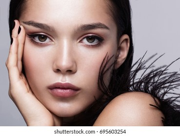 Close-up portrait of a beautiful fashion model in black with glossy makeup.