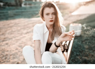Close-up portrait of a beautiful fashionable girl at sunset near the beach with a cigarette