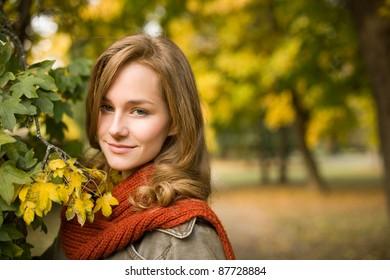 Closeup portrait of beautiful fashionable woman in autumn park.