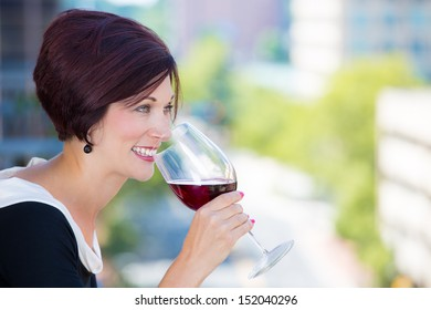 A close-up portrait of a beautiful female, businesswoman relaxing on a balcony on a sunny summer day,drinking red wine, isolated on a background of city buildings and green trees. Urban lifestyle