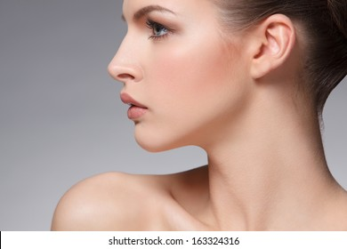 closeup portrait of beautiful female face over gray background