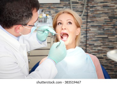 Close-up portrait of beautiful female patient visit at the dentist for check up at dentist office.