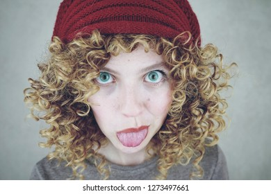 Close-up portrait of a beautiful and funny young woman with blue eyes and curly blonde hair sticking out her tongue wearing a red woolen cap