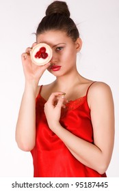 close-up portrait of beautiful girl with dark hair , in a red dress with cookies in hand. Photographed in a studio against a plain background