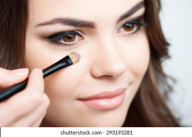 Close-up portrait of beautiful girl doing make-up. Someone is holding brush and touching it to her cheek carefully. Isolated on grey background