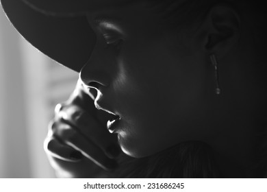 Close-up portrait of a beautiful girl in a fashionable hat, black and white
