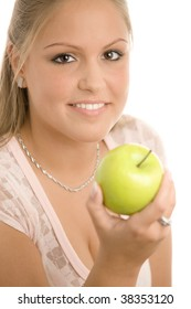 Closeup portrait of beautiful girl holding a green apple, smiling. Selective focus on girl, isolated on white background.