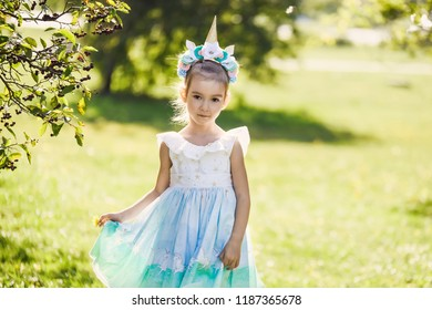 close-up portrait of a beautiful girl in a romantic blue cute dress with in a green autumn garden park  smiling sunny day celebrates Halloween with unicorn