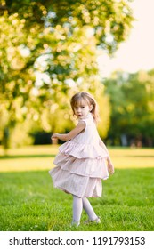 close-up portrait of a beautiful   girl in a romantic pink cute dress with in a green yellow autumn garden park posing and smiling