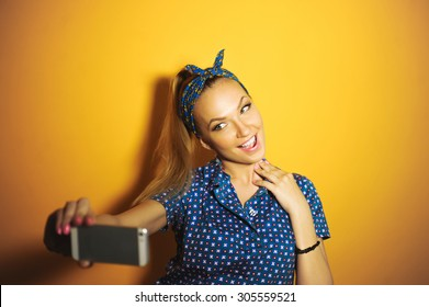 close-up portrait of a beautiful girl in the studio Young sexy hipster stylish bright on a yellow background with pink lips and manicured with a phone does selfi
