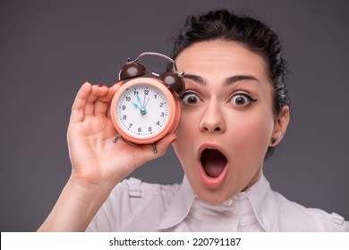 Close-up portrait of beautiful girl surprised looking at you and holding an alarm clock in her hand, with copy place isolated on grey background concept of time management