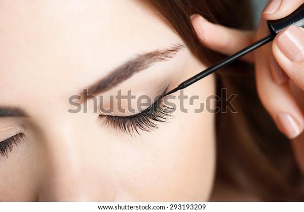 まぶたに黒いアイライナーを触れる美しい女の子の接写。彼女は目を閉じている