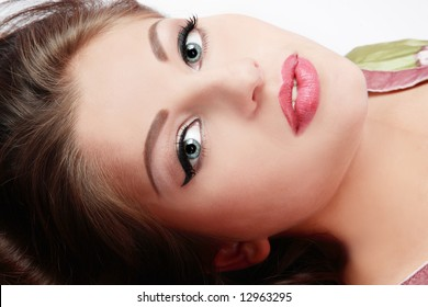 Close-up portrait of beautiful girl with trendy makeup lying in white background