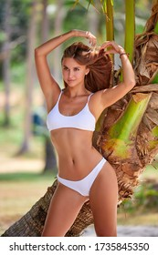 Close-up portrait of beautiful girl in white bikini posing near palm tree at the tropical beach