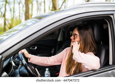 Close-up portrait of beautiful happy and laughing with all teeth young Caucasian woman is sitting in car and talking on mobile phone. Lifestyle, traveling and communication concept.