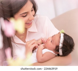 Closeup portrait of beautiful happy mother with cute little daughter on hands, child care, young loving family concept