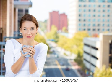 Closeup portrait of beautiful, happy, relaxed woman holding a cup of coffee, enjoying a weekend on sunny day, on balcony of her apartment isolated on city background. Urban life style of businesswoman