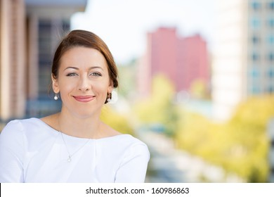 Closeup portrait of a beautiful, happy, smiling, relaxed business woman, enjoying a weekend on a sunny day, on a balcony of her apartment isolated on city background. Urban life style of businesswoman