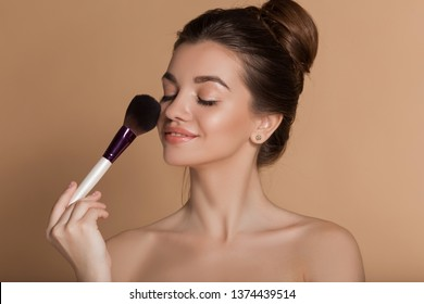 Closeup portrait of beautiful happy young girl with perfect skin is holding makeup brush in hand. Isolated on beige. Beauty and cosmetics concept.