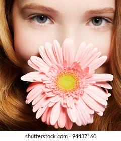 closeup portrait of beautiful healthy redhead teen girl with gerbera flower