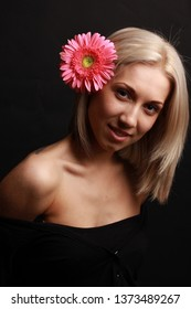 Closeup portrait of beautiful healthy woman with stylish make-up and pink gerbera flower. Cosmetics and cosmetology concept. Clean face, Natural skin.