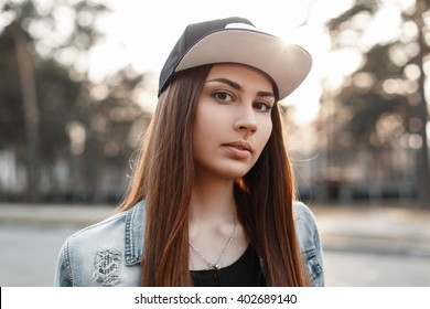 Close-up portrait of a beautiful hipster girl in a black baseball cap and torn blue jeans jacket at sunset