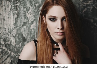Close-up portrait of a beautiful hipster woman with piercings in the nose over grunge background. Beauty, make-up. Fashion. Gothic style.