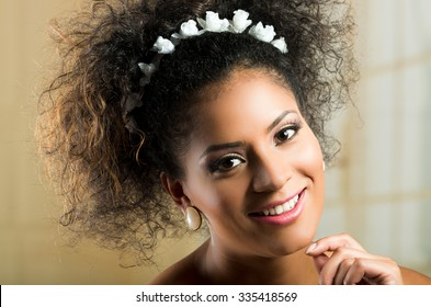 Closeup portrait of beautiful hispanic brunette young woman with curly hair wearing a floral hairband
