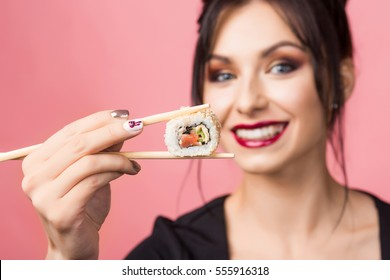 Close-up portrait of a beautiful lady, she eating delicious sushi on sticks and smiling widely, white teeth, perfect face, a healthy Japanese food, makeup, hairstyle, sexy girl, Diet, dieting concept