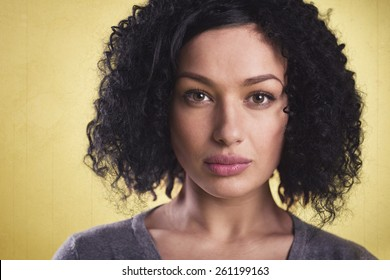 Closeup portrait of a beautiful latina woman with dark skin looking serious, isolated on yellow background.