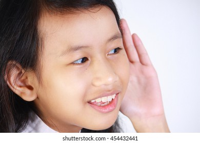 closeup portrait of beautiful little Asian girl listening carefully with her hand to ear gesture trying to hear secretly interesting information conversation news